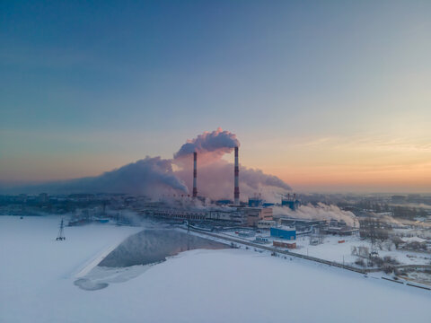 Smoke stacks over sunrise sky background at freezing weather morning with haze. Energy generation and air environment pollution industrial scene.
