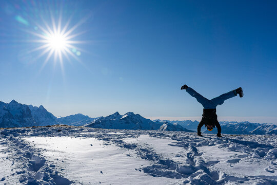 handstand straddle on snow caped mountain peak with blue sky and bright sunbeams. Copy space, concept.