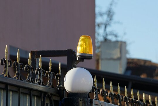 one yellow signal light and a white round glass shade on a black iron wall of a fence with sharp rods