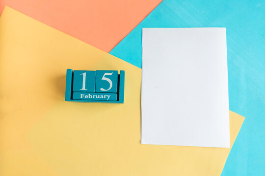 February 15. Blue cube calendar with month and date and white mockup blank on color geometric background.