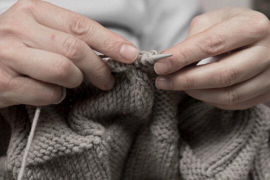 mujer haciendo punto con lana marron