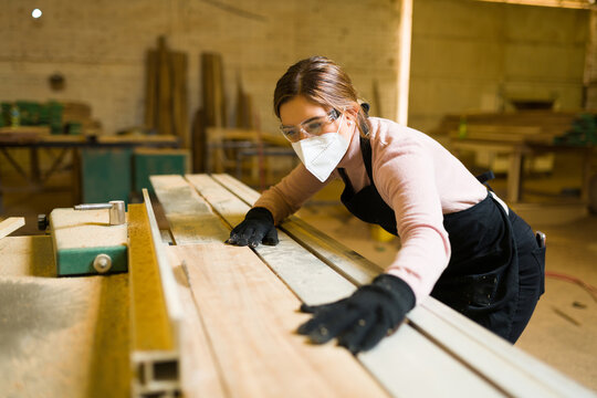 Beautiful worker wearing protective equipment and cutting wood