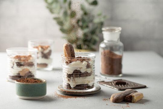 Classic italian dessert-Tiramisu in glasses with savoyardi cookies,mascarpone,cream liqueur and cocoa.Cocoa powder falling on dessert.Close-up.