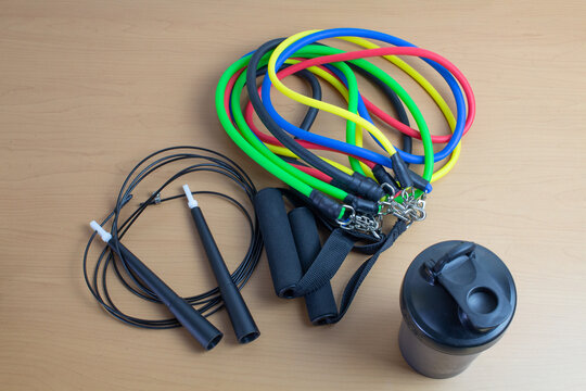 black plastic sports shaker, resistance bands, fast jump rope. fitness and training concept
