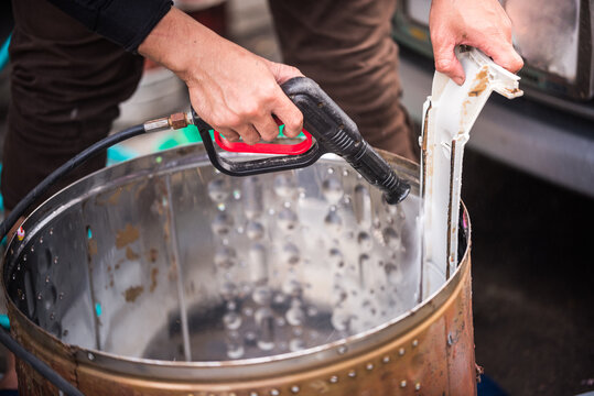 Asian man's hand held a high-pressure spray gun was spraying water onto the stain with the equipment in the washing machine drum.