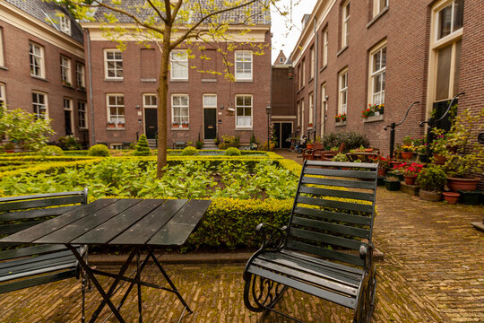 Close up image of rustic metal chair and table at acourtyard garden in a senior housing community. In the background there is  a well maintained garden, brick buildings and cobblestone ground.