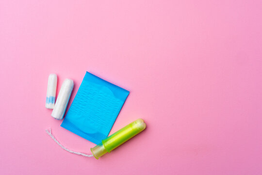 Female hygienic pad and tampons on pink background