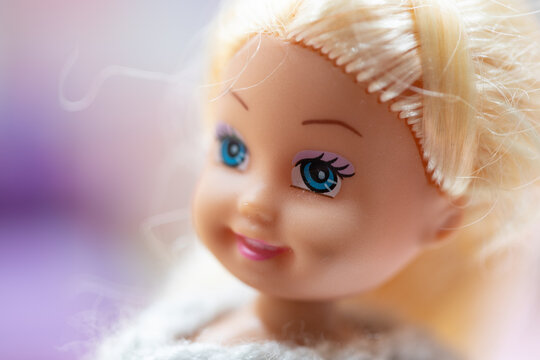 Close up of a small plastic doll with blond hair and blue eyes smiling against a pastel colored background.
