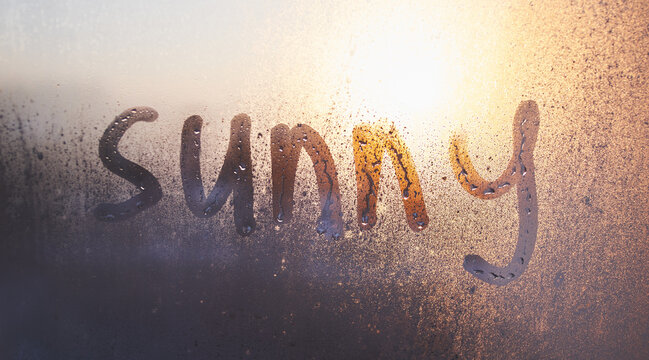 The sunny word on the steamy window with water drops on sunny background. fogged window at home