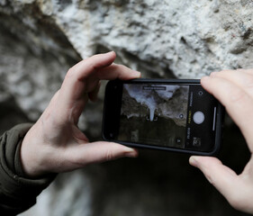 Fototapeta dłoń która trzyma telefon i robi zdjęcie