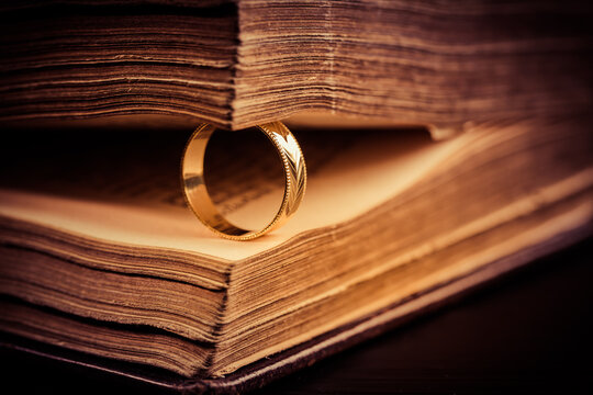 Golden ring between the pages of old book in vintage style