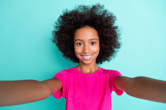 Photo portrait of smiling afro american girl taking selfie isolated on vivid cyan colored background