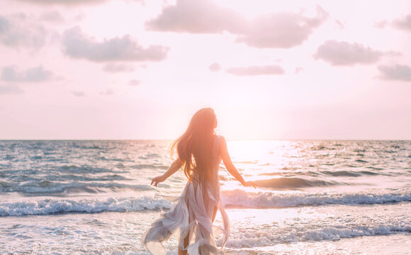 Silhouette of beautiful young happy woman tourist walks runs by coastline. girl admires beauty bright divine sun light sea sunset. Blue pink clouds sky. Fluttering long hair back view. silk dress fly