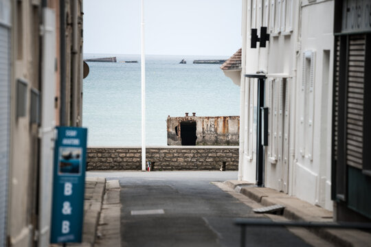 Mulberry floating harbour Normandy France street view of ocean concrete float ww2 defences on Atlantic wall at Arromanches along coastline from Second World War 2 allied invasion remain today