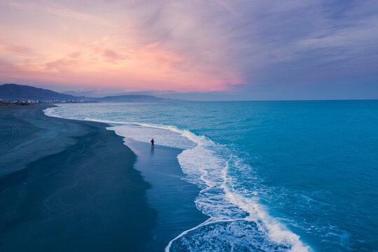 Uomo pesca da solo al tramonto in riva all'oceano