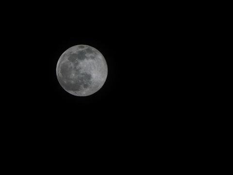 Full moon on dark black sky background