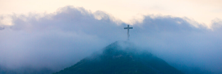 Fototapeta A single cross stands on a mountain engulfed in white clouds obraz
