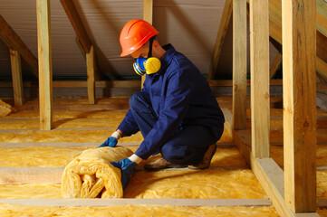 Obraz Man installing thermal roof insulation - fototapety do salonu