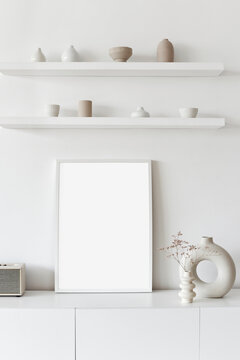 Blank picture frame mockup on white wall. White living room design. View of modern scandinavian style interior. Home staging and minimalism concept.