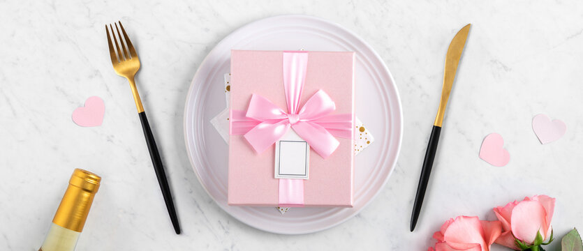 Plate with gift and pink rose for Valentine's Day special meal concept.