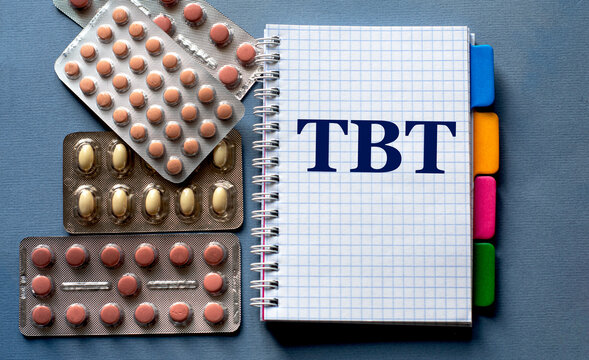 TBT - word in a notebook. Nearby are pills on a gray background