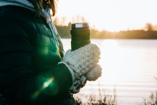 Swedish woman's hands in traditional nordic gloves holding a hot drink