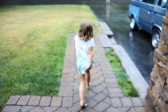 blurred image of girl running in  the rain in  springtime