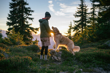 Male Hiker Petting Dog At Sunset In The Mountains Wall mural