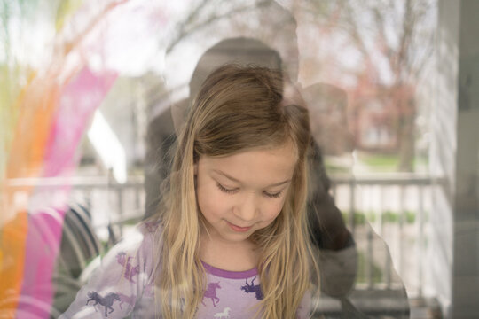 outside in view of blond girl painting rainbow on window