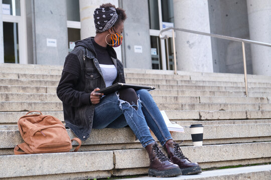 University female african student wearing protective face mask studying sitting on stairs outside on campus. New normal in college.