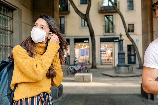 Woman putting on a mask by square in Barcelona