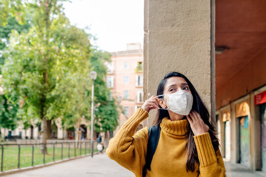 Woman putting on a mask by old buildings in Barcelona