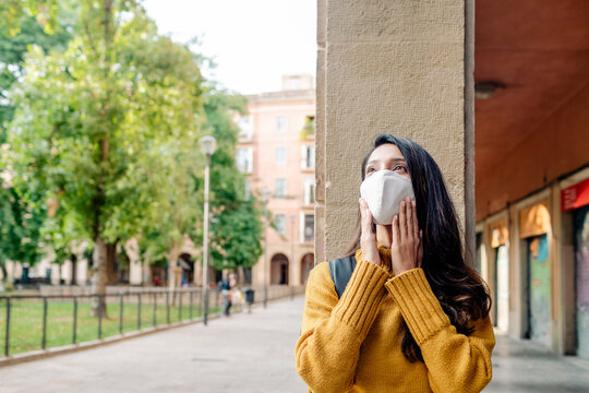 Thoughtful young woman wearing a mask by old buildings in Barcelona
