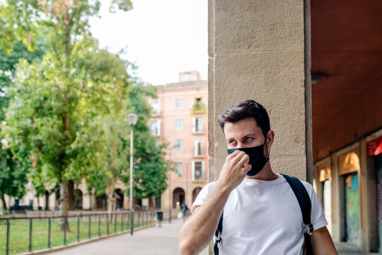 Handsome young man holding mask by square in old city