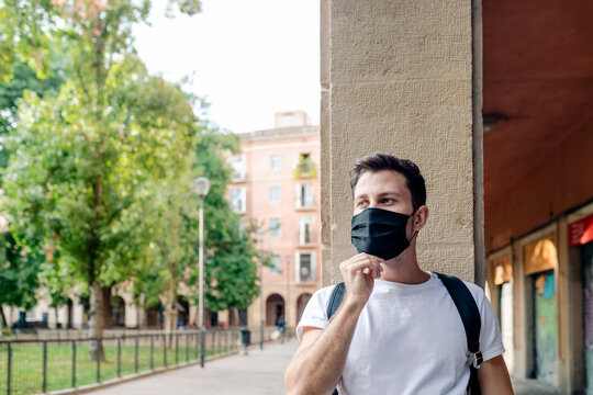 Handsome young man putting a mask by square in old city