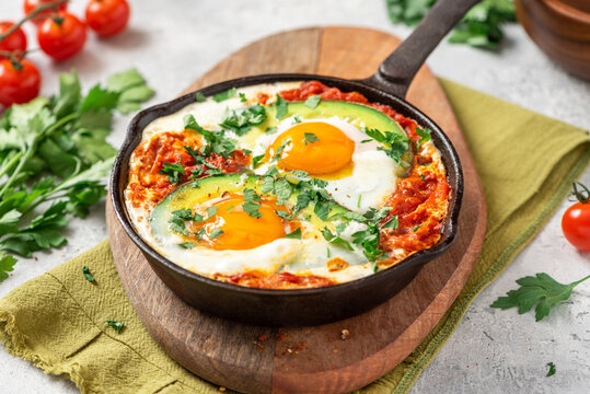 Shakshouka with avocado in a frying pan on a gray table close-up. Shakshouka of tomato sauce, eggs, spices, onions, garlic, and avocado. Tasty Maghreb style breakfast.