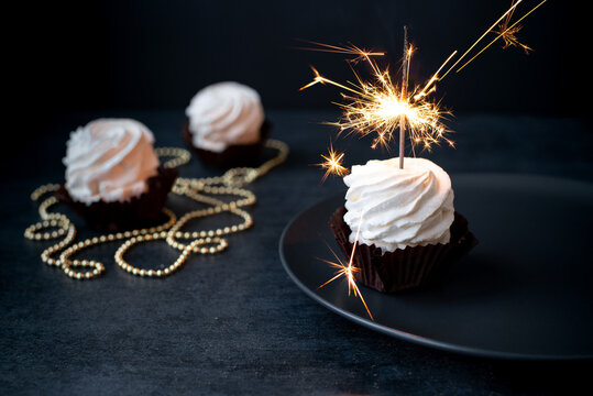 Delicious cupcakes with sparkler on dark background