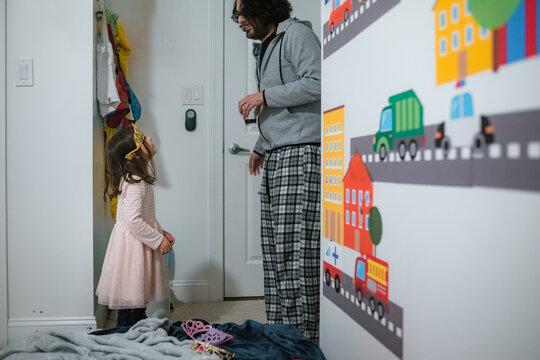 Little girl in tiara looking up at dad in domestic kids bedroom