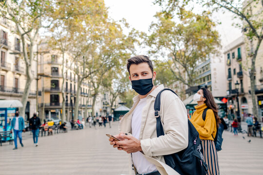 Man wearing mask finding address on phone in Las Ramblas