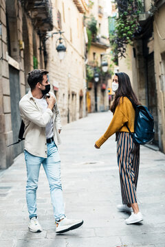 Friends walking meeting street social distance in historic European