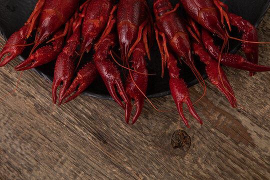 Boiled crayfish on black plate, shot from top on wooden table