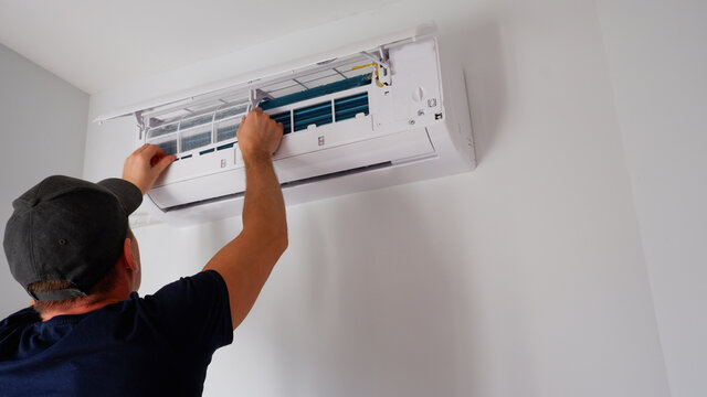 Maintenance of the air conditioner. A technician is cleaning the filter. View of the hands from the back.