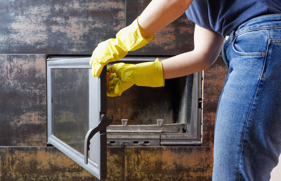 Close up of young woman in jeans, yellow gloves is cleaning the fireplace. Modern fireplace with glass.
