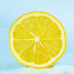 Juicy yellow slice of lemon on blue background