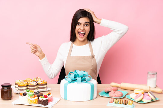 Pastry chef with a big cake in a table over isolated pink background surprised and pointing finger to the side