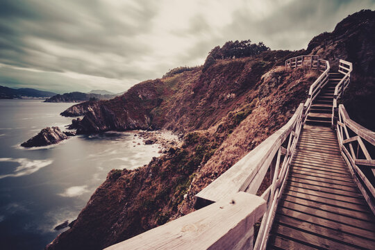 Wooden path along the steep coast in Galicia in northern Spain.