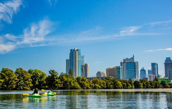People kayaking on Ladybird Johnson Lake in Austin, Texas  with the Austin skyline in the background.
