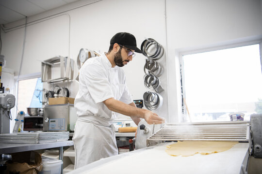 Male baker sprinkling pastry dough with flour in bakery kitchen