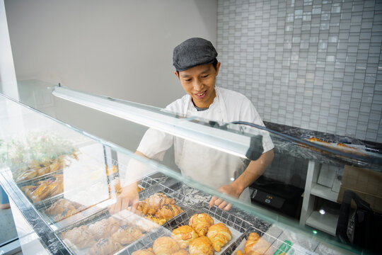 Smiling male baker arranging French pastries in bakery display case
