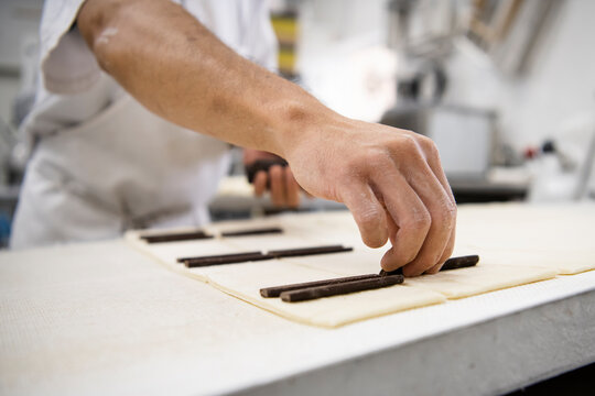 Close up male baker preparing pain au chocolate pastries in bakery
